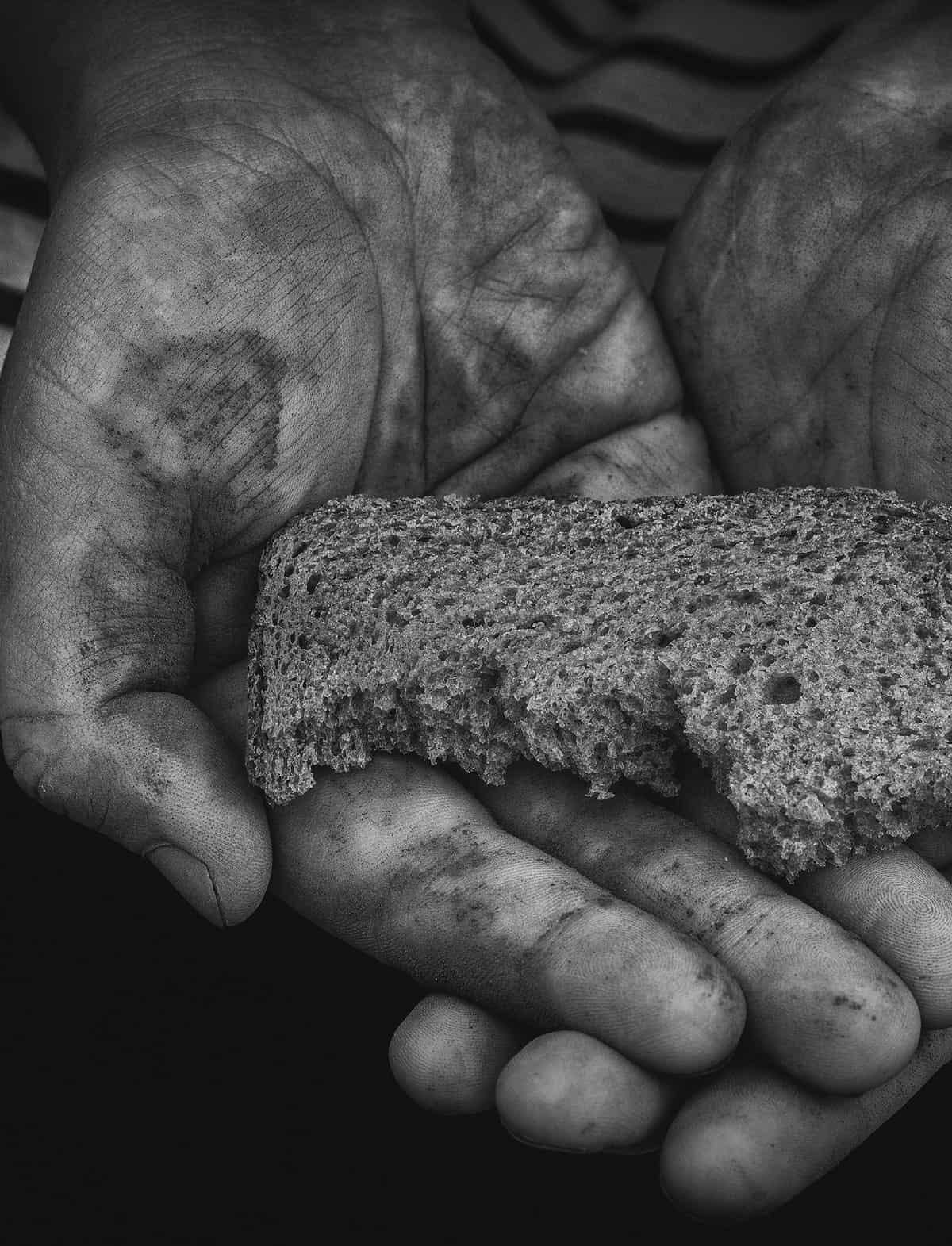 Zwei Hände halten ein angebissenes Brot, schwarz-weiß
