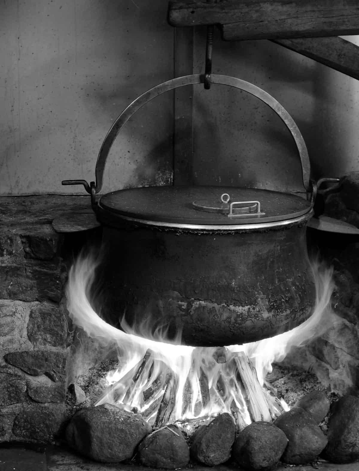 Kessel hängt über Feuer, schwarz-weiß